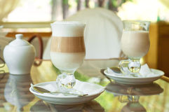 Coffee in the morning. Two cappuchino coffee standing on a glass table in a cafe on a bright sunny day Royalty Free Stock Photography