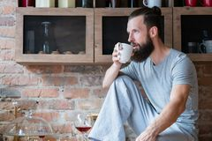 Coffee morning contemplation intention man cup. Coffee time. Morning contemplation. Intention. Young bearded hipster with white cup sitting on kitchen counter stock images