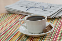 Coffee and the Morning Paper. A cup of coffee with the morning newspapers on placemat on a wooden table Royalty Free Stock Photo