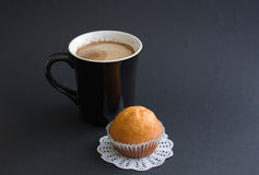 Coffee  with muffin. Coffee with milk in a black cup with muffin on a black background Royalty Free Stock Image