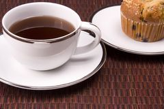 Coffee and Muffin. White coffee mug on placemat background with a muffin Royalty Free Stock Photo