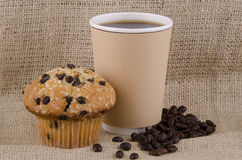 Coffee and muffin. Coffee cup and chocolate chips muffin on jute background Royalty Free Stock Images