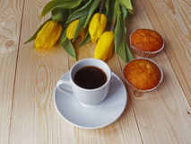 Coffee and muffins on the table. In the background tulips Royalty Free Stock Photo