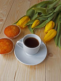 Coffee and muffins on the table. In the background tulips Royalty Free Stock Images