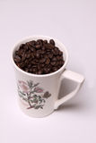 Coffee Mug. A mug full of coffee beans on a white background Royalty Free Stock Photography