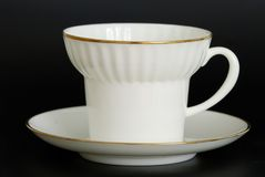 Coffee mug. White coffee cup from thin porcelain with a thin gold strip on a black background royalty free stock photo