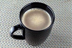 Coffee Mug. Fresh brewed coffe in a black mug. Close up shot, shallow focus Stock Photography