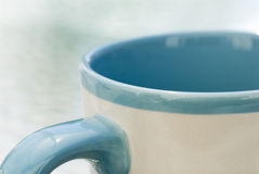Coffee mug. A close up, partial view of a coffee mug with blue trim Stock Images
