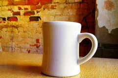 Coffee mug. Cup of coffee against worn interior loft brick wall royalty free stock images