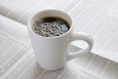 Coffee mug. A coffee mug rests on the financial pages of the morning paper Royalty Free Stock Photos
