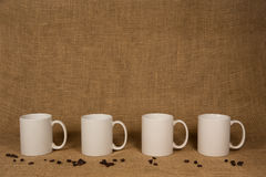 Coffee Mug Background - White Mugs and Beans. Coffee Mug Background. Four white mugs and coffee beans in front of burlap. Copy space on and above the mugs royalty free stock photos