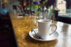 A coffee mug on a bar table. A cup of filter coffee with plate and spoon on a bar table in Vancouver Royalty Free Stock Images