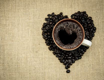 Coffee mug on beans shaped like a heart Stock Images