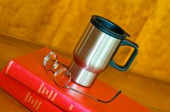Coffee mug on books. A view of a silver coffee mug and eyeglasses laying on leather bound official company records on a counter top in the office of the Royalty Free Stock Photos