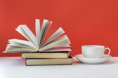 Coffee mug and books on a red background. A mug of coffee is on the table. An open book rests on a pile of books. Red background. Copy Space Royalty Free Stock Photo