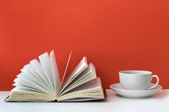 Coffee mug and books on a red background. A mug of coffee is on the table. An open book rests on a pile of books. Red background. Copy Space Stock Image