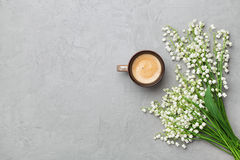 Coffee mug with bouquet of flowers lily of the valley on gray stone table top view in flat lay and minimalistic style. Royalty Free Stock Photos