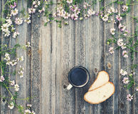 Coffee mug with bread on weathered wooden background with field
