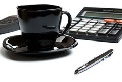 Coffee mug, calculator, pens, phone Royalty Free Stock Images