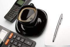 Coffee mug, calculator, pens, phone Royalty Free Stock Photos