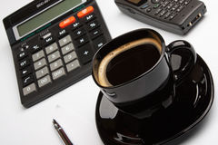 Coffee mug, calculator, pens, phone Stock Images