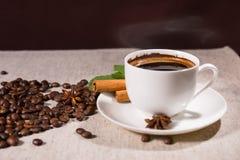 Coffee mug by cinnamon sticks and loose beans Stock Photos