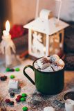A coffee mug with cocoa on the Christmas lights background with marshmallows. A coffee mug with cocoa on the Christmas lights and candles background with Stock Image
