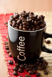 Coffee mug with coffee beans Stock Images