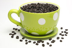 Coffee Mug With Coffee Beans. Yellow polka dot coffee mug filled with coffee beans on white background Stock Photos