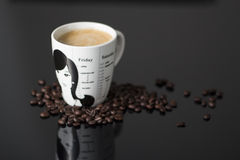 Coffee mug and coffee beans. Black and white coffee mug filled with fresh coffee/ latte and is surrounded by coffee beans. The mug has an illustration of a woman Stock Image