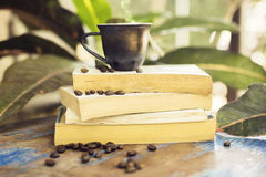 Coffee mug, coffee beans and books on a wooden table Royalty Free Stock Photo