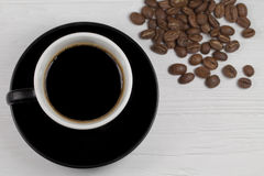 Coffee mug and coffee beans on wood backgound Royalty Free Stock Photo