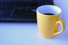 Coffee mug with copy space. Laptop on background. stock images