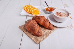 Coffee mug with croissant, jam, orange and notes good morning on white rustic table from above, cozy and tasty breakfast, vintage Royalty Free Stock Photos