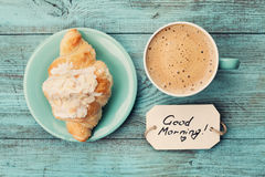 Coffee mug with croissant and notes good morning on turquoise rustic table from above, cozy and tasty breakfast. Vintage toned