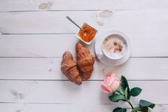 Coffee mug with croissant, rose, jam and notes good morning on white rustic table from above, cozy and tasty breakfast, vintage to Royalty Free Stock Photography