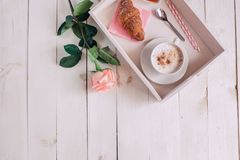 Coffee mug with croissant, rose, jam and notes good morning on white rustic table from above, cozy and tasty breakfast, vintage to Stock Photo