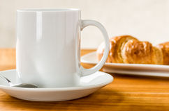Coffee mug with croissants. A coffee mug with croissants Royalty Free Stock Images