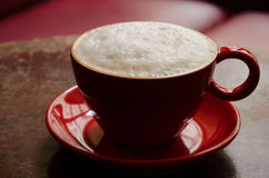 Coffee mug with frothed milk in an atmospheric cafe. Mug with coffee and frothed milk in a dark atmospheric cafe illuminated through the window, which is Stock Images