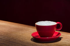 Coffee mug with frothed milk at the bar. A single mug with coffee and frothed milk in a dark cafe Royalty Free Stock Photography