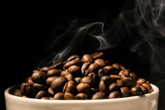 Coffee mug full of coffee beans with smoke Royalty Free Stock Image