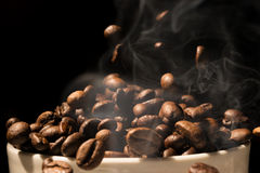 Coffee mug full of coffee beans with smoke Stock Photography