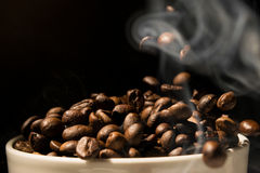 Coffee mug full of coffee beans with smoke Royalty Free Stock Images