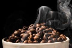 Coffee mug full of coffee beans with smoke Stock Image