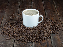 Coffee mug with grains on dark wood background Royalty Free Stock Photos