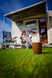 Coffee Mug on grass. Family vacation travel, holiday trip in mot Royalty Free Stock Photo