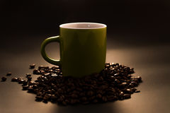 Coffee mug. Green coffee mug with roasted coffee beans isolated on black background Stock Images
