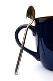 Coffee mug handle and spoon. Closeup of the handle of a blue coffee mug and a spoon on an white background Royalty Free Stock Photography
