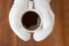 Coffee mug in hands mittens outdoor in winter on Christmas Eve Stock Image