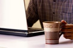Coffee mug held by a man working on a laptop computer in the background Stock Photography